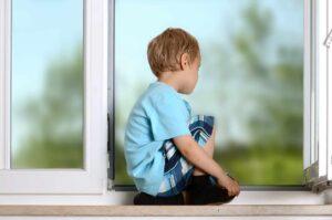Chłopczyk siedzący na parpecie otwartego okna