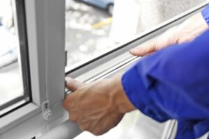 Pracownik serwisu uszczelnia okno z PCV